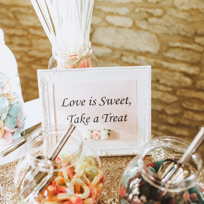 "A sign that says ""love is sweet, take a treat"" on a pick and mix station"