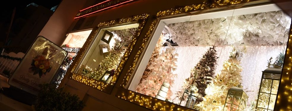 The front of a Christmas shop with two beautifully decorated window displays