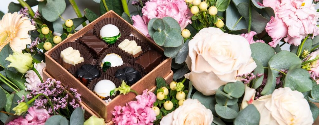 Six handcrafted chocolates on different shades of pink fresh flowers