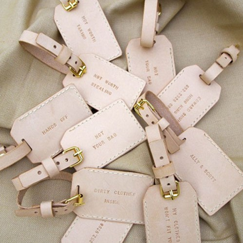 A handful of cream luggage tags with quotes written on them