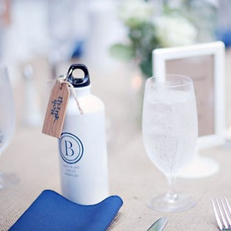 A metal bottle of water with a blue personalized message