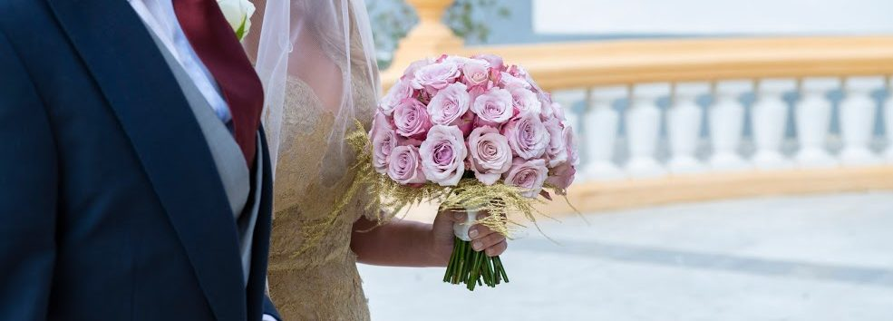 A bride with golden dress, walking into the Church with a pink rounded bridal bouquet.