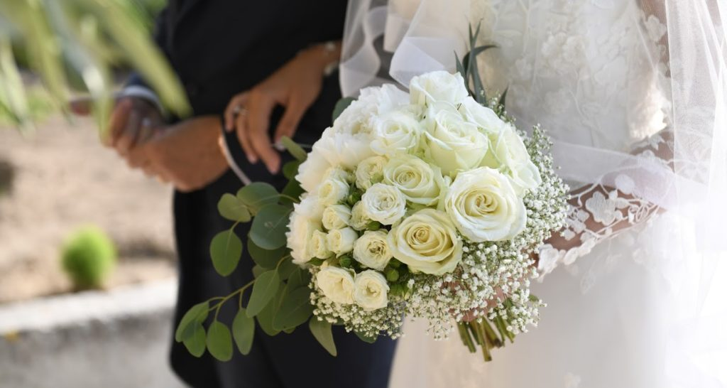 A bride walking with her dad while holding an all white bridal bouquet