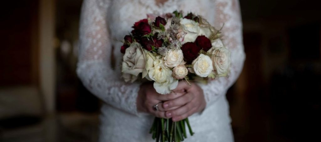 A bride holding a bridal bouquet with burgundy roses.