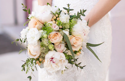 A small bridal bouquet with cream roses, light pink flowers and green foliage.