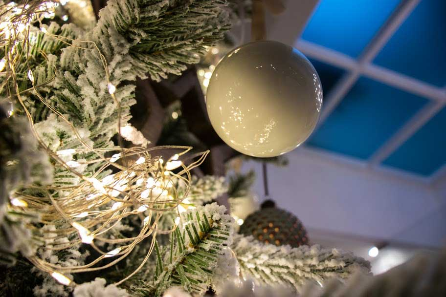 A cluster of lights on a snowy Christmas tree shining through a white bauble.