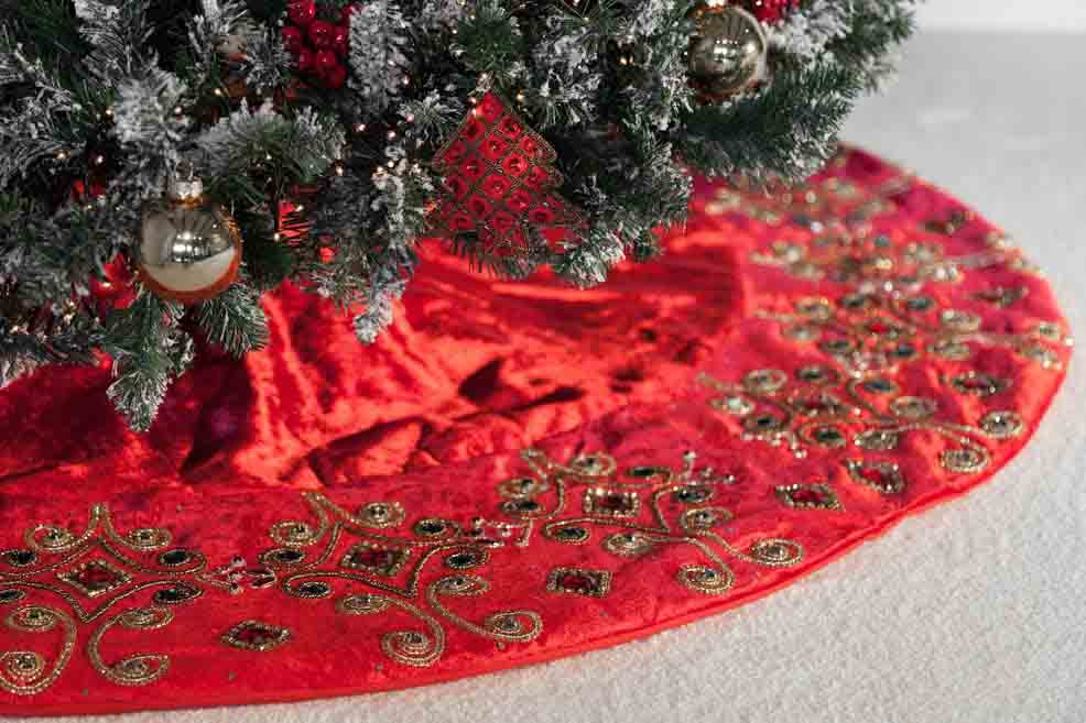 A red handcrafted Christmas tree skirt under a snowy artificial Christmas tree.