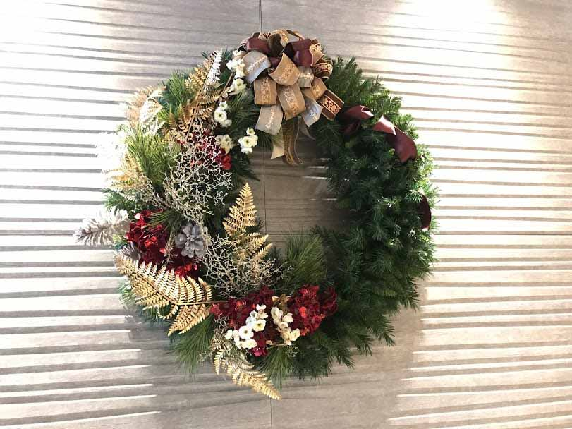 A semi decorated Christmas wreath with gold and silver foliage.